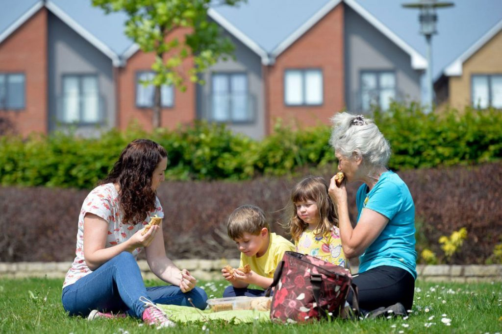mother grandmother and two children having picnic infront of houses