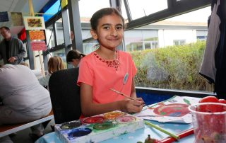 Girl sat at table painting at Ebbsfleet Community Event