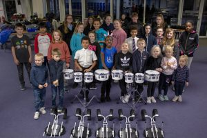 group of band children standing infront of some instruments