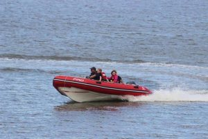 people on the water in a red motor power dingy