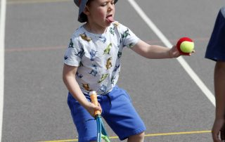 Boy in a hat playing tennis