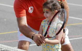 Man showing girl how to play tennis