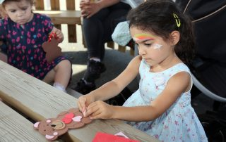 Girl with face paint crafting