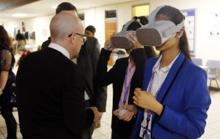 Man showing two girls virtual reality masks at the Ebbsfleet Jobs Fair