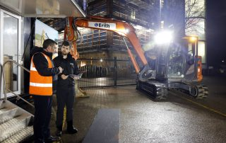 Two men talking next to a digger