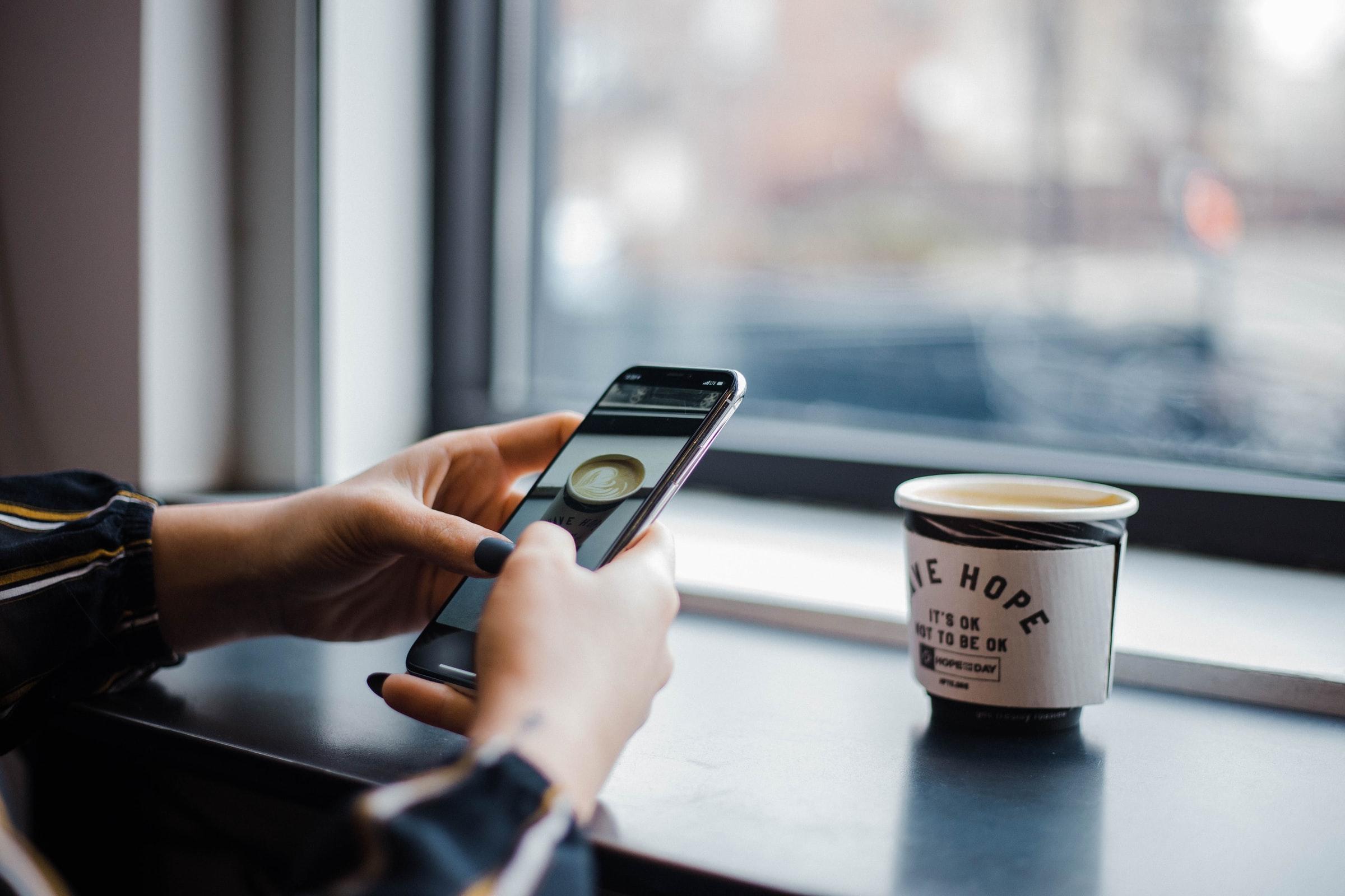 A phone near a coffee cup