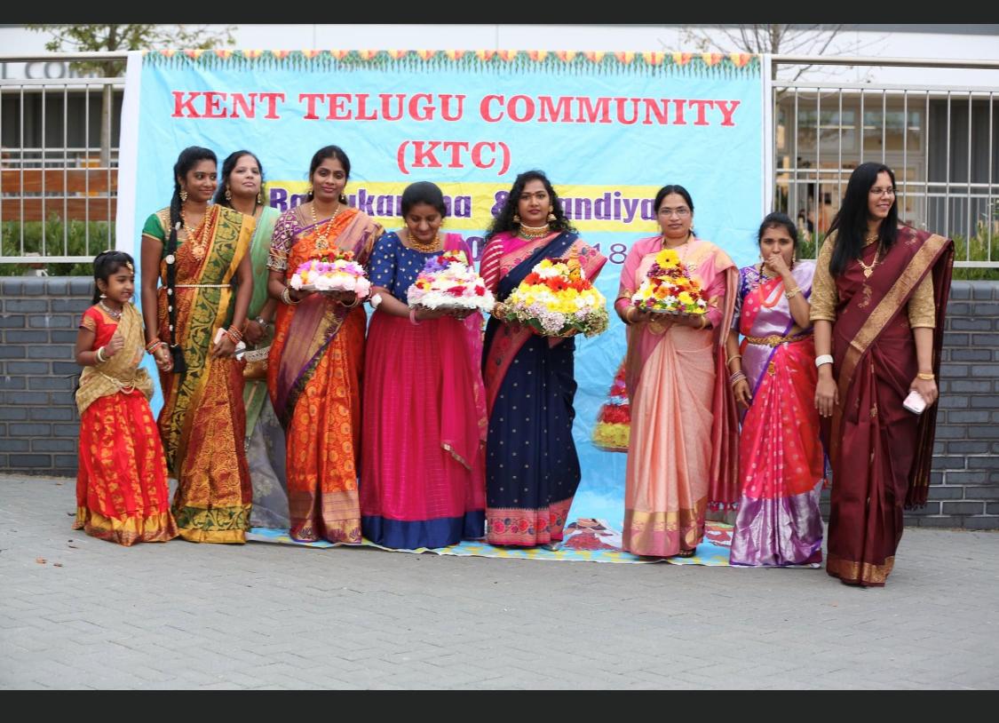 group of women in sari dresses infront of Kent Telugu Community banner